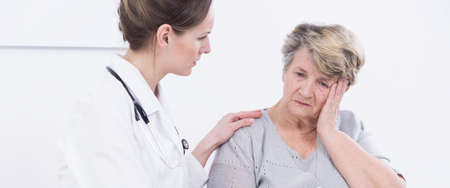 geriatrician: Young pretty doctor in duster. Older patient with headache visiting physician in cabinet
