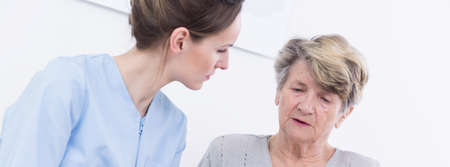 geriatrician: Elderly sad woman talking with her young pretty doctor about her problems at hospital