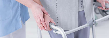 patient care: Close-up of carer helping older disabled woman to walk with walker