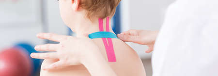 taping: Pediatric physiotherapist using physio tapes on little childs neck