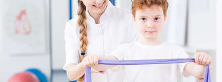 pediatric: Little boy doing an exercise with the help of pediatric physiotherapist