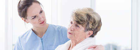 geriatrician: Caring young physician listening her worried patients complains about health problems Stock Photo