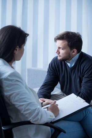 verticales: Hombre joven con problemas en el gabinete del psicoterapeuta
