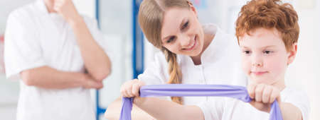 elastic band: Child exercising with personal physiotherapist at medical clinic Stock Photo