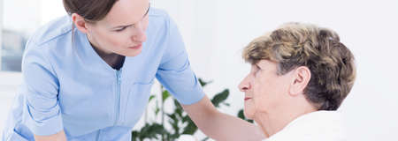 geriatrician: Helpful young pretty nurse and older sick patient in hospital waiting for surgery Stock Photo