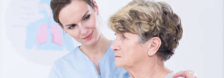 geriatrician: Older worried woman sitting in hospital. Young pretty doctor supporting her sad patient before surgery