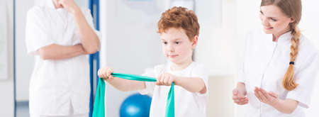 elastic band: Little boy exercising with elastic band during physiotherapy