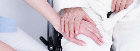 caregivers: Close-up of older disabled patient holding her young caregivers hand Stock Photo