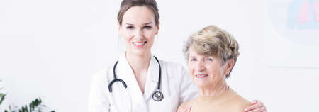 geriatrician: Happy senior lady and her beautiful young doctor in a duster with stethoscope