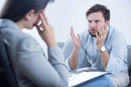 El hombre joven enojado quejándose de su psicólogo sobre sus problemas