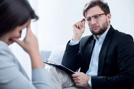 psychiatrist: Smart experienced psychiatrist solving young depressed womans problems Stock Photo
