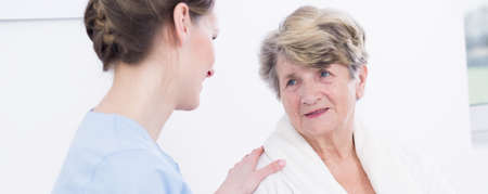 geriatrician: Aged troubled woman in clinic waiting for surgery. Talking with caring young doctor Stock Photo