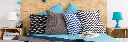 double beds: Trendy arrangement of bed patterned cushions Stock Photo