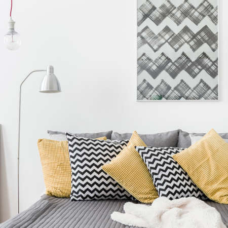 bedspread: Various cushions on the bed in cozy bedroom Stock Photo