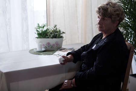 Sad elderly lady in black with a handkerchief Stock Photo