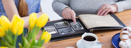 generation gap: Cropped picture of an elderly woman showing an old photo album to her granddaughter