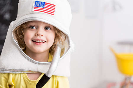 themed: Shot of a cute little boy wearing a toy space helmet Stock Photo