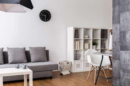 Moderne, minimalistische woonkamer met rustruimte, racks en bureauhoek