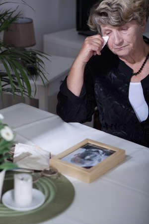 to pass away: Woman looking at the photo of her dead husband