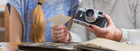 old photographs: Cropped picture of an elder woman holding a camera and showing old photographs to her granddaughter Stock Photo