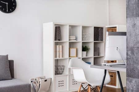 luz natural: esquina brillante de una sala de estar con mesa de ordenador, silla y estante grande, blanco