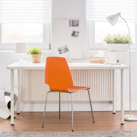 lightings: Image of white desk with new orange chair Stock Photo