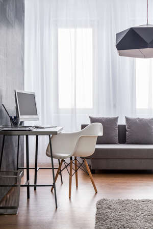 living room sofa: Minimalist workspace with grey desk and white designer chair arranged as a part of a very bright living room