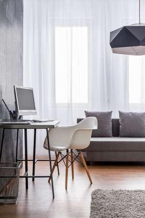 Minimalistische werkruimte met grijze bureau en een witte design stoel ingericht als een onderdeel van een zeer lichte woonkamer