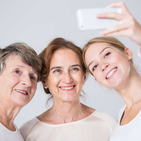3 generation: Smiling granddaughter taking perfect family selfie - horizontal view