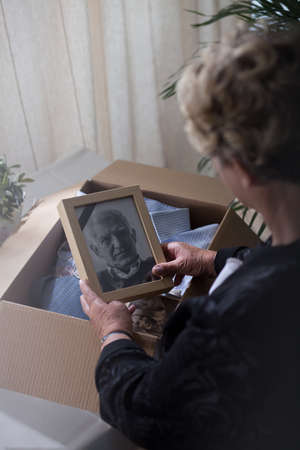 memento: Elederly widow with a photo of her lost husband
