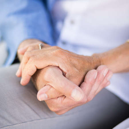 Close-up of loving senior couple holding hands Stock Photo