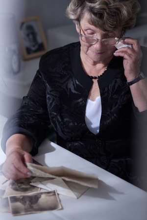 cartas antiguas: Mayor mujer viuda leyendo viejas cartas de su marido
