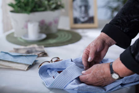 to pass away: Old womans hands on mens shirt belonging to her dead husband