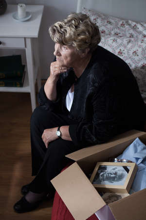 to pass away: Grandmother with box of keepsakes of her lost husband Stock Photo