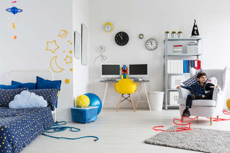 boy bedroom: Shot of a little boy sitting in an armchair in his space themed bedroom Stock Photo