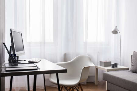natural light: Very clear interior with large, bright window shaded with net curtain, with computer desk, chair and grey sofa