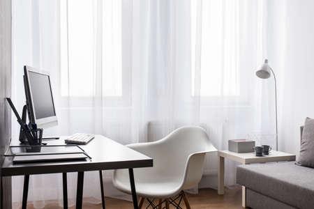 Zeer duidelijk interieur met grote, heldere venster schaduw met vitrage, met computer bureau, stoel en grijs sofa Stockfoto