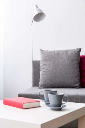 Corner of a very bright room with a book and two coffee cups on a white coffee table in the foreground and a grey sofa behind