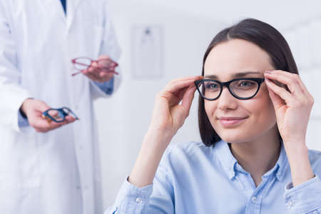 Woman trying on black frames, optician holding blue and red frames