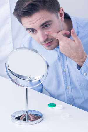 putting in: Man putting in contact lens, sitting in front of a mirror
