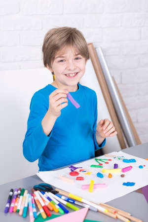 beside table: Happy, small boy drawing a picture, standing in light interior beside table Stock Photo