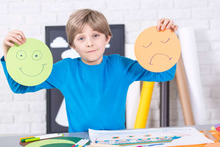 beside table: Boy holding a picture of a happy and sad face, standing beside table in light interior Stock Photo