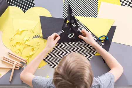 amarillo y negro: Muchacho que hace corte de papel, uso de papel negro y amarillo Foto de archivo