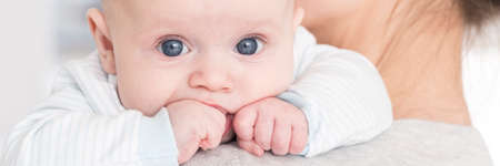 그의 어머니의 어깨에 신생아 유아의 근접 초상화, 그의 입에 그의 작은 주먹을 가하고
