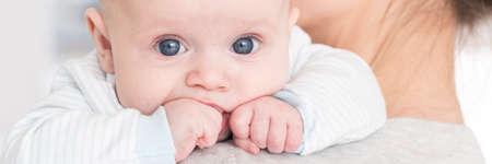 Primer plano retrato de un bebé recién nacido en el hombro de su madre, poniendo su pequeño puño en la boca