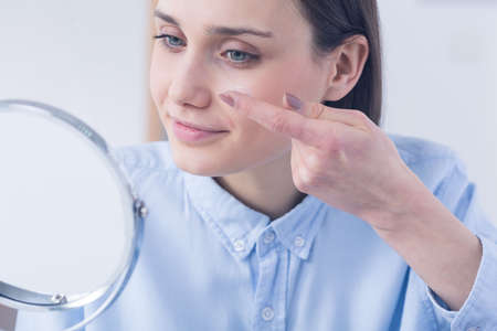 Woman inserting contact lens, sitting in front of a mirror Stockfoto