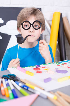 beside table: Small boy holding paper pipe and glasses, standing beside table