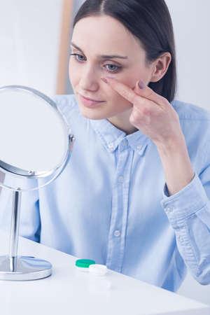 lentes de contacto: Mujer que toma las lentes de contacto, que se sienta delante de un espejo
