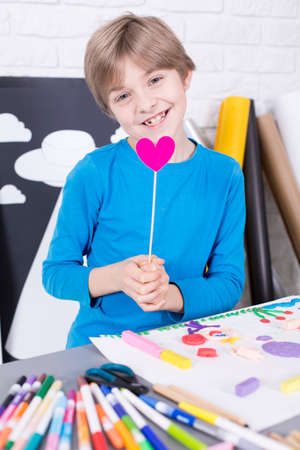 beside table: Small boy smiling, holding paper heart, standing beside table