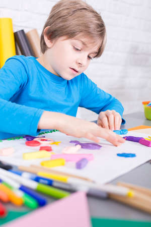 beside table: Small boy sitting beside table, preparing a picture, using a plasticine